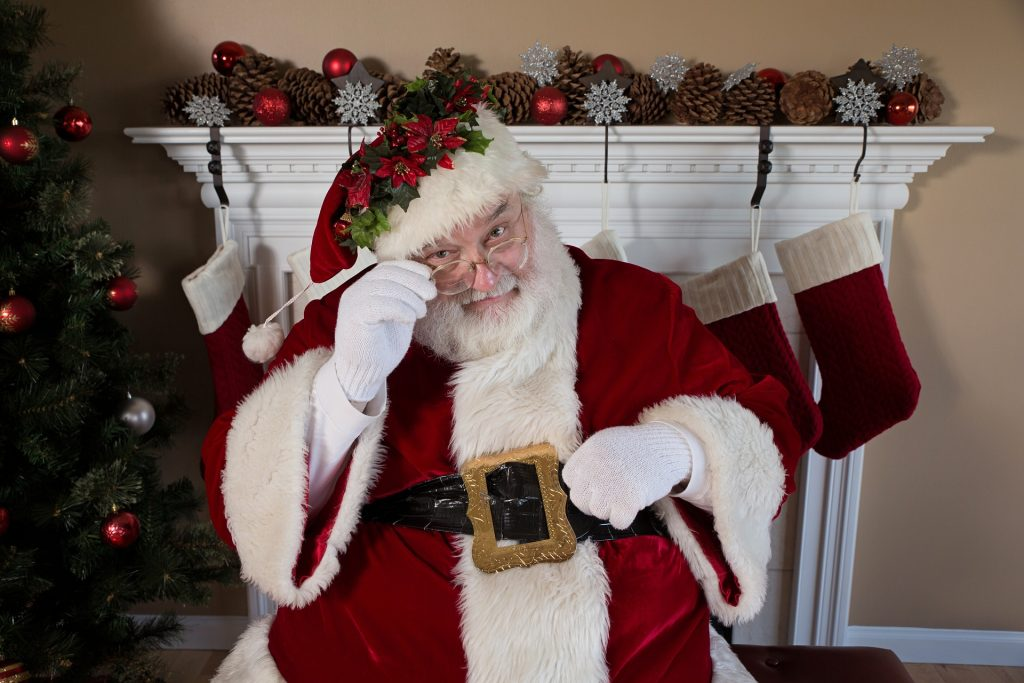 Santa Claus adjusting his glasses in front of a fireplace.