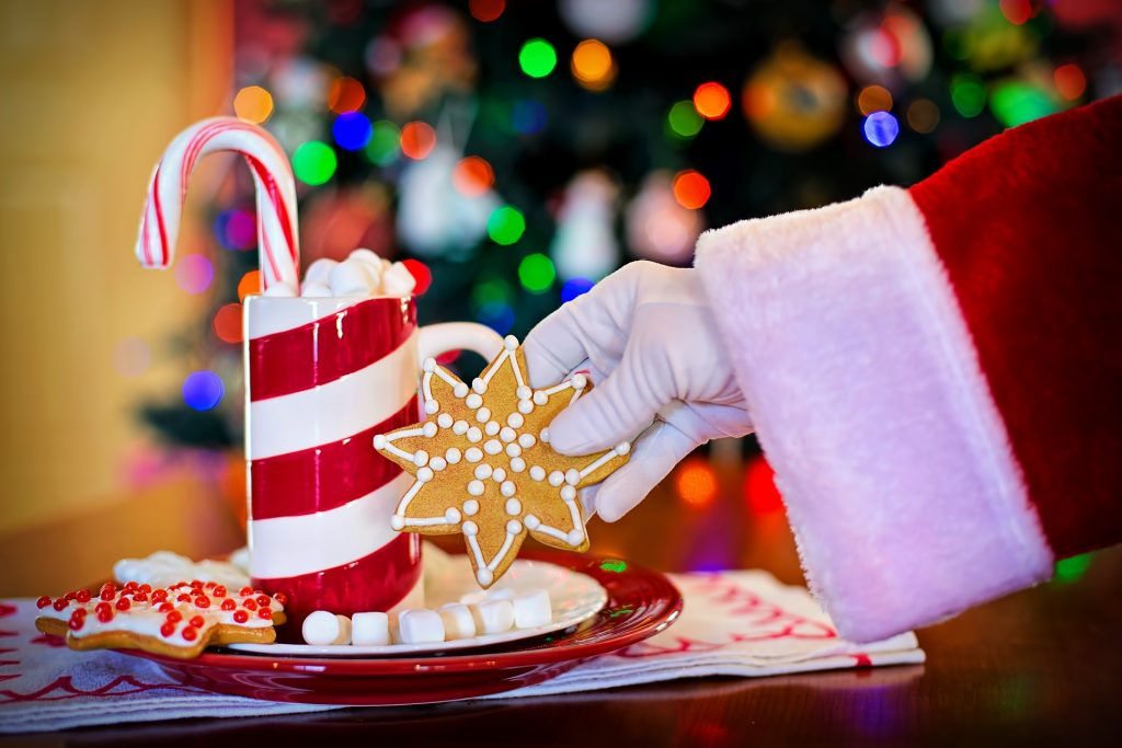 Santa's hand holding a Christmas Cookie